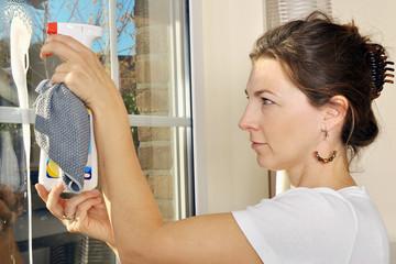 Frau beim Fenster putzen mit Fensterspray