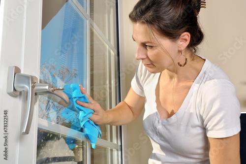 canvas print picture Frau bei Hausarbeit putzt Fenster mit Fenstertuch