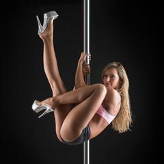 Beautiful woman performing pole dance. Studio shot on black back