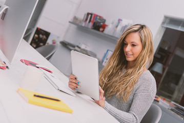 Young woman portrait working with tablet in modern office.