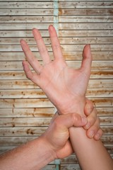 Composite image of male hand grabbing female wrist