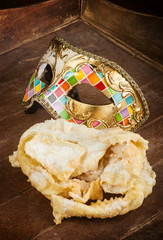 Fried pastry of italian carnival with venetian mask.