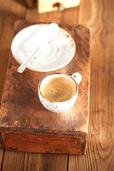 A cup of black coffee on old textured wood