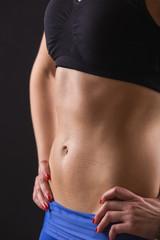 Sporty Female Sweaty Abdomen on Black Background