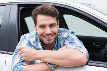 Young man smiling and holding key