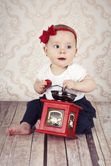 Pretty little baby girl playing with coffee grinder