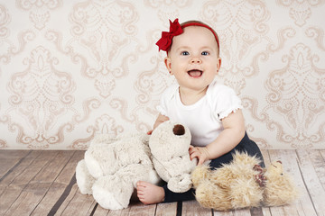 Laughing little baby girl with plush toys