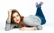 Young woman lying on white studio background.