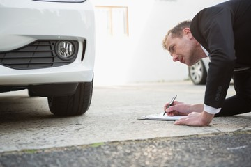 Businessman examining car tire while writing on clipboard