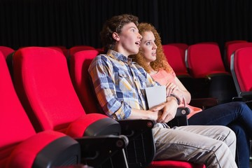 Astonished young couple watching a film