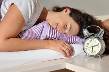 Frau liegt erholt und vergnüngt im Bett