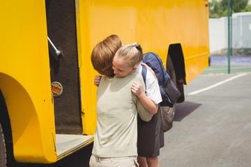 Mother hugging her daughter by school bus