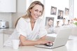 Composite image of happy woman using laptop at counter