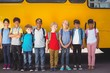 canvas print picture - Cute pupils smiling at camera by the school bus