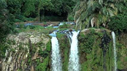 High scenic waterfalls from a rocky stream; wild tropical nature