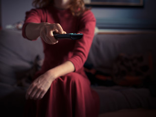 Young woman sitting on sofa and watching TV