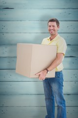 Composite image of man holding moving boxes