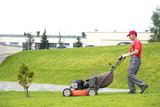 City landscaper cutting grass with lawn mower