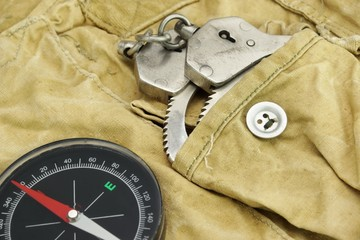 Compas and Handcuffs On The Weathered Backpack