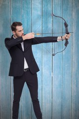 Composite image of businessman shooting a bow and arrow