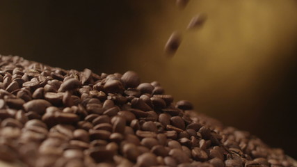 Coffee beans falling rotating and twisting tabletop