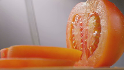 Knife cutting tomato macro