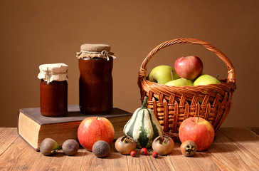 Jam into jars, books, and fruits in wicker basket