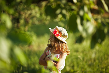 Girl in a hat stands among the foliage
