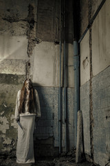 zombie girl with loong hair in an abandoned building holding kni