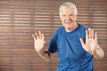 Alter Mann macht Gymnastik in Fitnesscenter