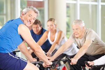 Trainer mit Senioren im Fitnesscenter
