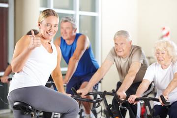 Trainerin im Fitnesscenter hält Daumen hoch