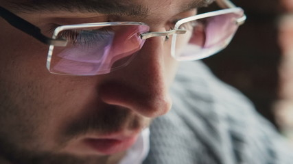 Close-up of a man with the reflection of his tablet screen in