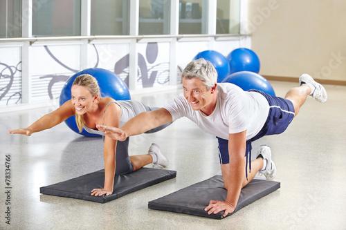 Leinwanddruck Bild Mann und Frau machen Gymnastik im Fitnesscenter