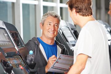Trainer im Fitnesscenter berät Senioren