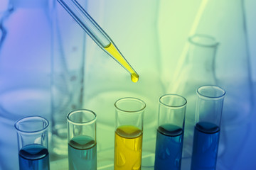 Pipette adding yellow fluid to one of several test-tubes with