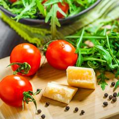 Food preparation, tomato rucola and Parmesan salad