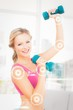 Composite image of athletic blonde lifting dumbbells and smiling