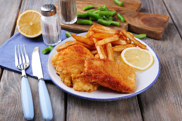 Breaded fried fish fillets and potatoes with asparagus and