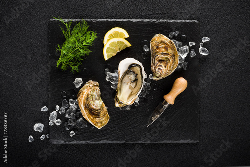 Fresh oysters on a black stone plate top view - 78336767
