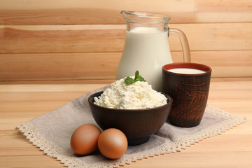 Cottage cheese in clay bowl with jug of milk and eggs