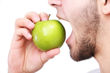 Man biting fresh green apple with healthy teeth isolated