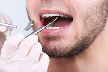 Examine of young man by dentist on white blurred background