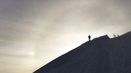 Hiking silhouette at the sunset on a snowy mountain
