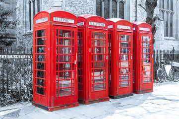 Row of red british telephone boxes on desaturated background