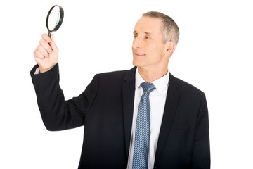 Portrait of businessman with a magnifying glass