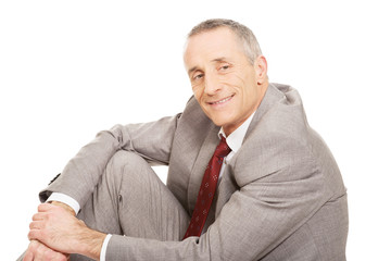 Side view happy businessman sitting on the floor