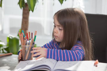 Child is Painting on a coloring book