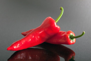 two red pepper chilli is laying on a table