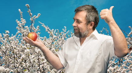 middle-aged man in white shirt with red apple